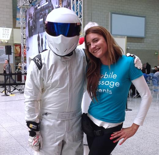A Mobile Massage Events employee at an event with the Stig.