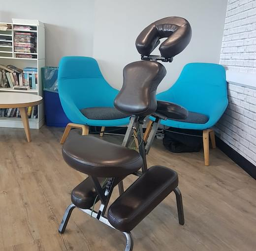 A mobile massage therapy chair in an office with some chairs and a table.