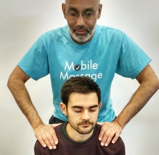 A man receiving a shoulder massage from another man.