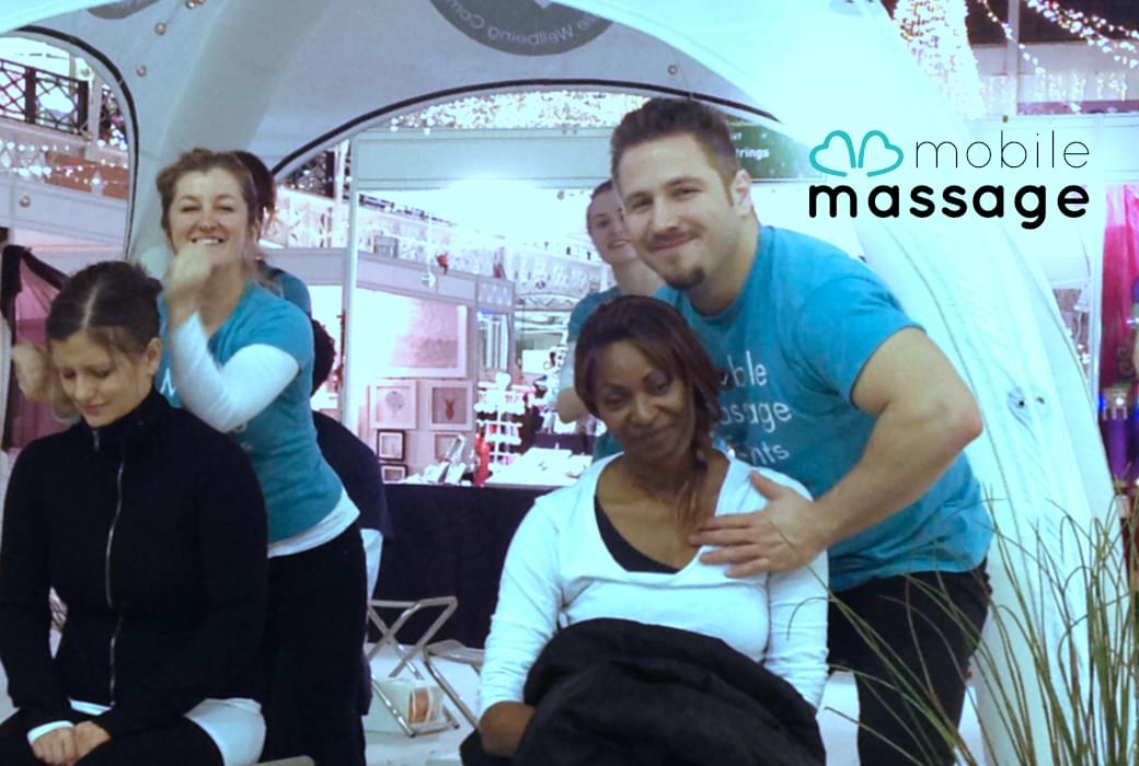 Two mobile massage events team members performing a massage for guests at an event.